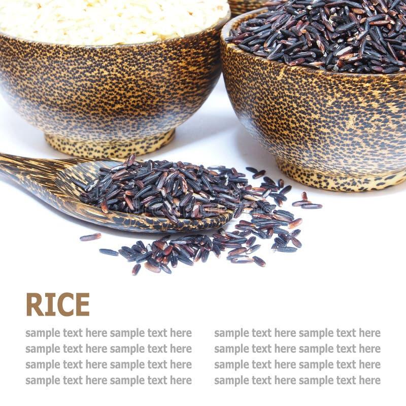 Grani di riso in ciotola di legno e cucchiaio di legno isolati su bianco fotografia stock libera da diritti