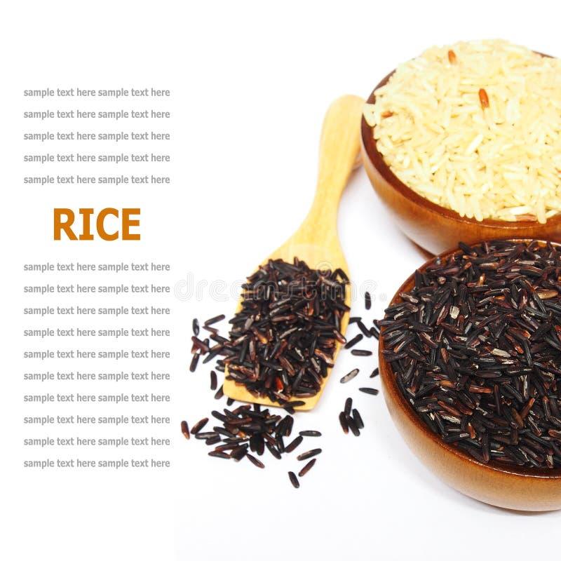 Grani di riso in ciotola di legno isolata su bianco immagine stock