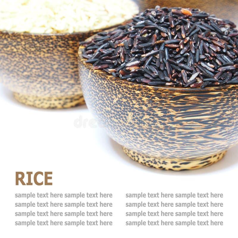 Grani di riso in ciotola di legno isolata su fondo bianco immagini stock libere da diritti