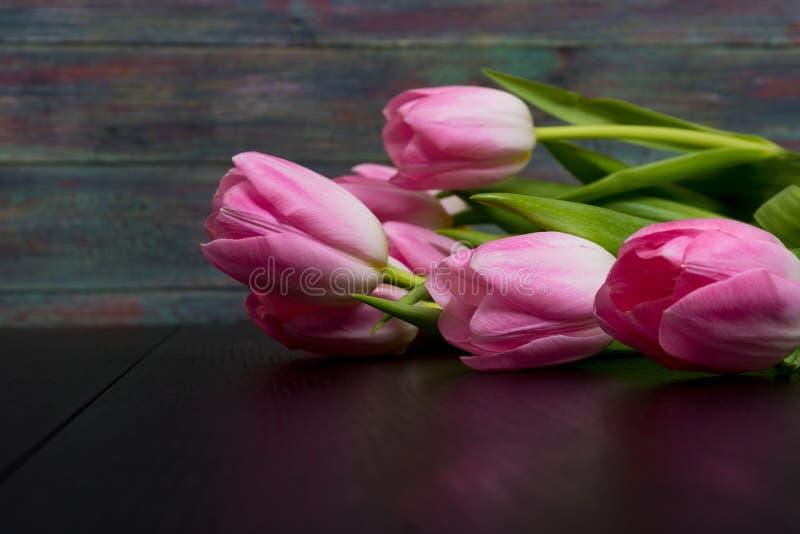 Granica od jaskrawych różowych tulipanów kwitnie na czarnym drewnianym backgroun zdjęcie royalty free