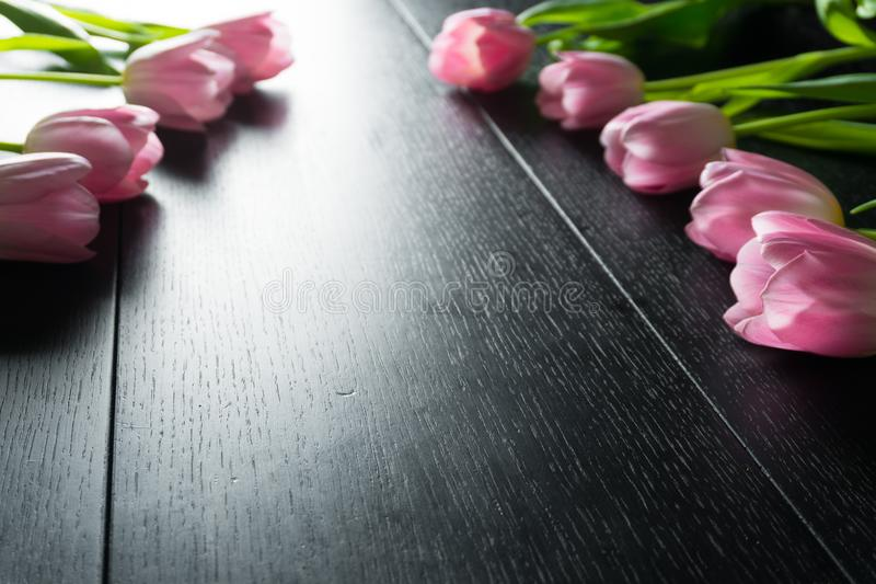 Granica od jaskrawych różowych tulipanów kwitnie na czarnym drewnianym tle obrazy stock