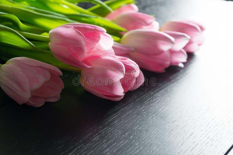 Granica od jaskrawych różowych tulipanów kwitnie na czarnym drewnianym tle zdjęcie royalty free