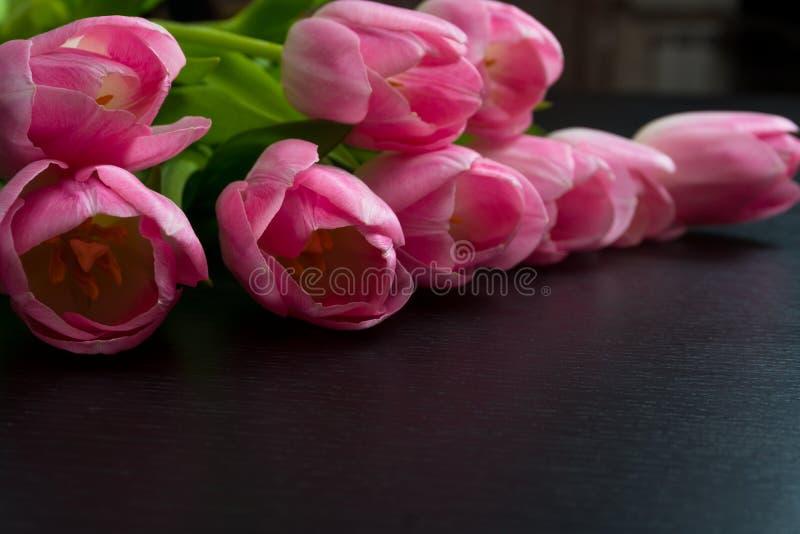 Granica od jaskrawych różowych tulipanów kwitnie na czarnym drewnianym tle zdjęcia royalty free
