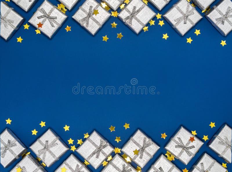 Granica srebni błyszczący prezenty i złote gwiazdy na błękitnym tle dekoracje świąteczne ekologicznego drewna obraz stock
