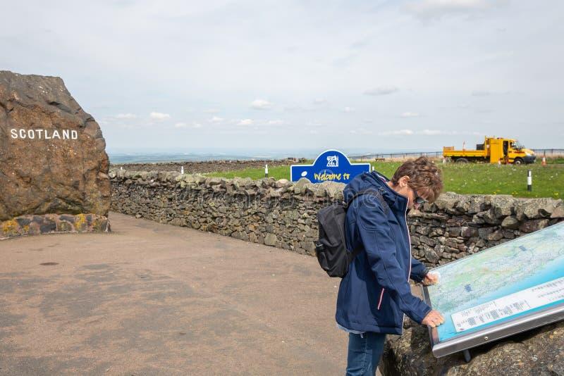 Graniczy między Anglia i Szkocja z skałą i czytelniczą kobietą zdjęcia stock