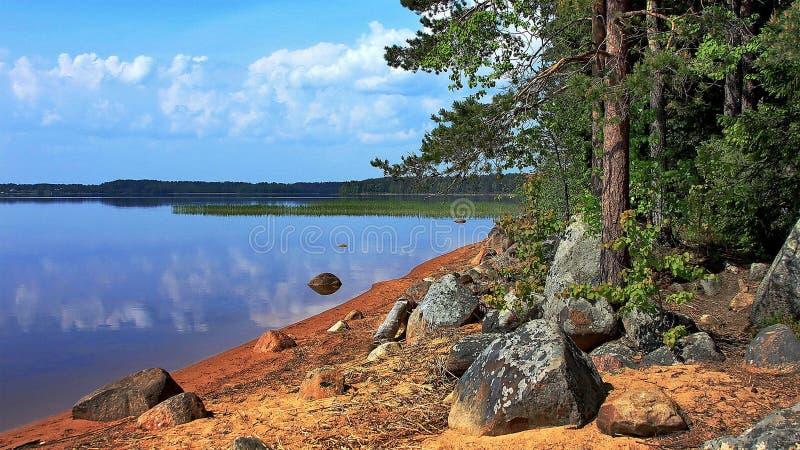 Granietkeien op de kust van een bosmeer De gouden Herfst Bezinning van de hemel in water De laatste warme de herfstdagen stock fotografie