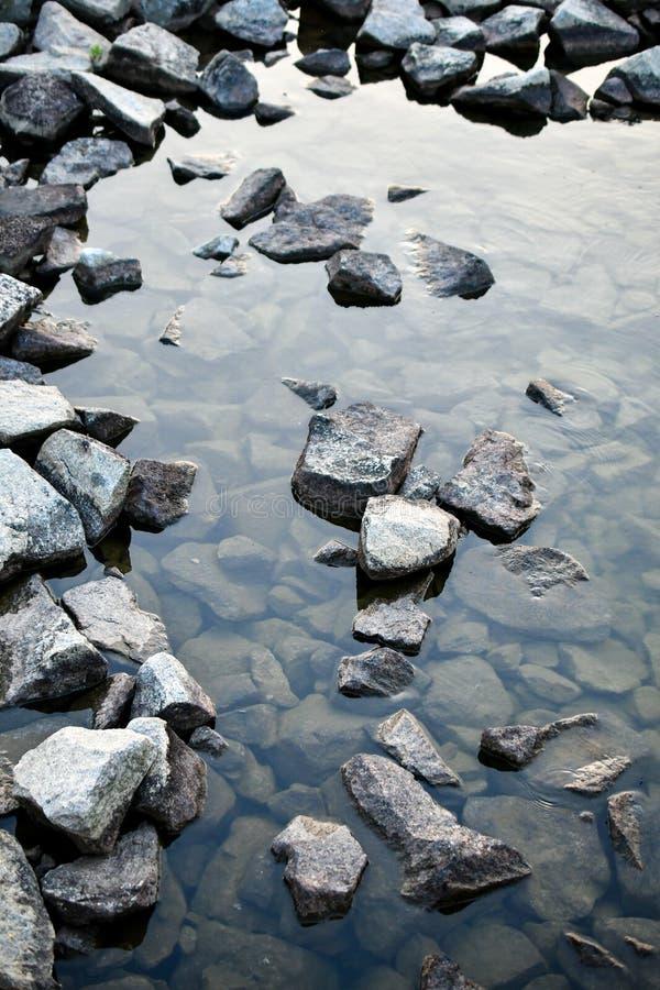 Granit vaggar i vatten arkivbild