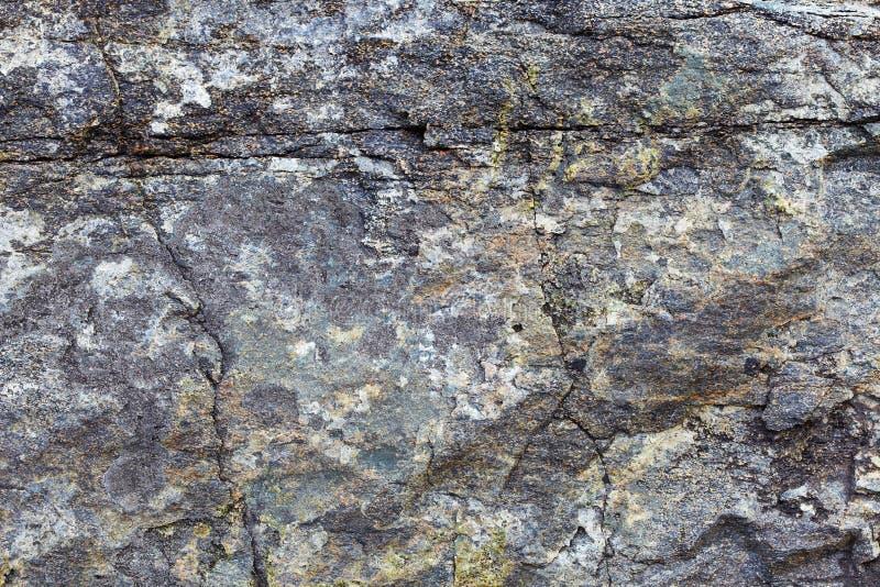 Granit vaggar med fläckar och sprickor - en naturlig bakgrund royaltyfri foto