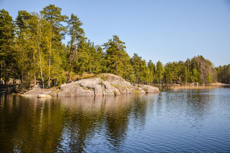 Picturesque stone on the banks of the river Vuoksa. Granite banks of the nothern river Vuoksa cut to clear water royalty free stock photography