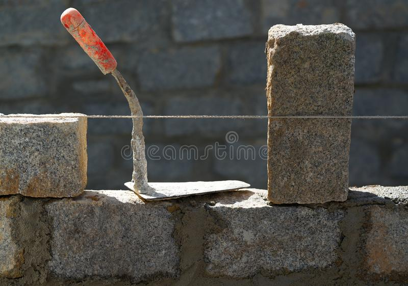Granite blocks wall construction with mortar stock photography