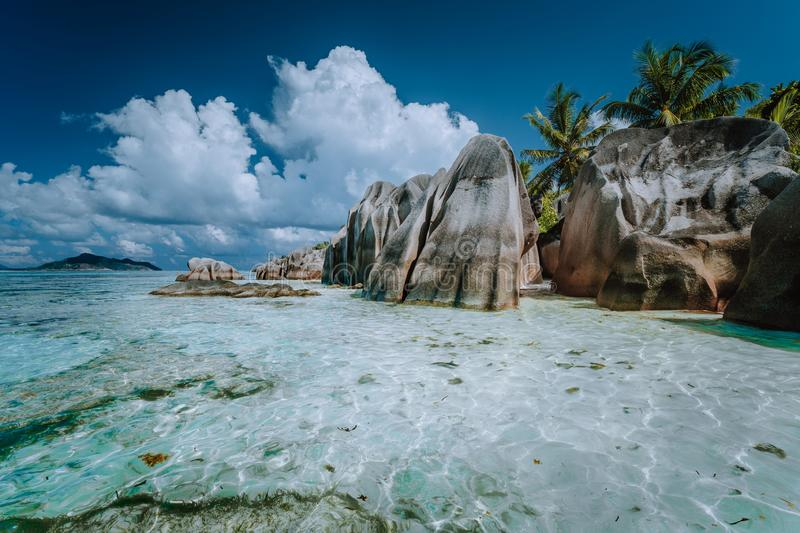 Granite boulders in shallow ocean water and white cloudscape on amazing Anse Source D`Argent tropical beach, La Digue. Seychelles. Luxury exotic travel concept royalty free stock images