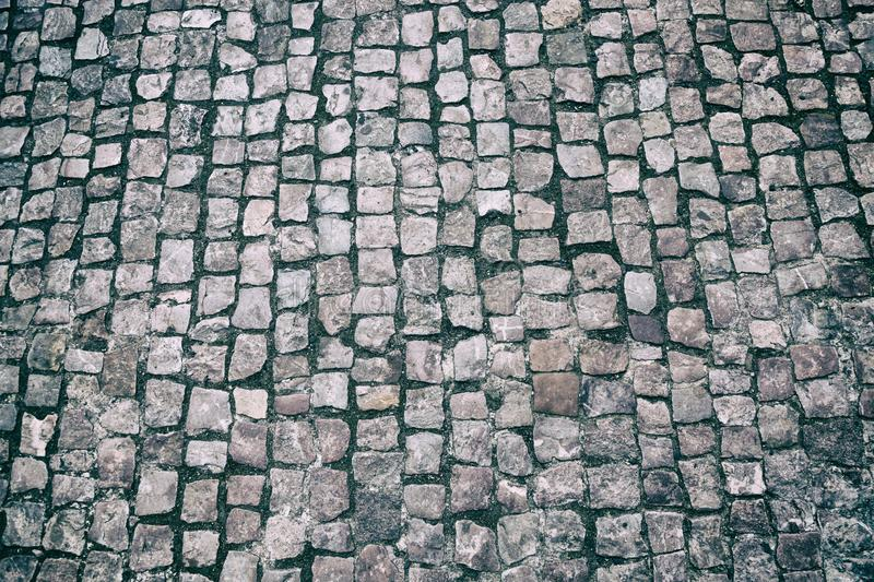 Granite cobble stoned pavement background. Stone pavement texture. Abstract background of old cobblestone pavement close-up in Pra stock photography