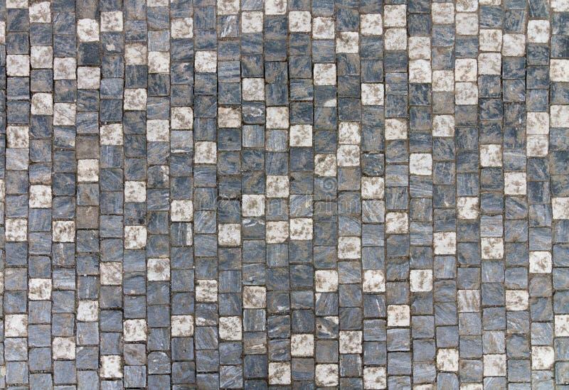 Granite cobblestoned pavement background with regular design. Dark and light cobble stones royalty free stock photos