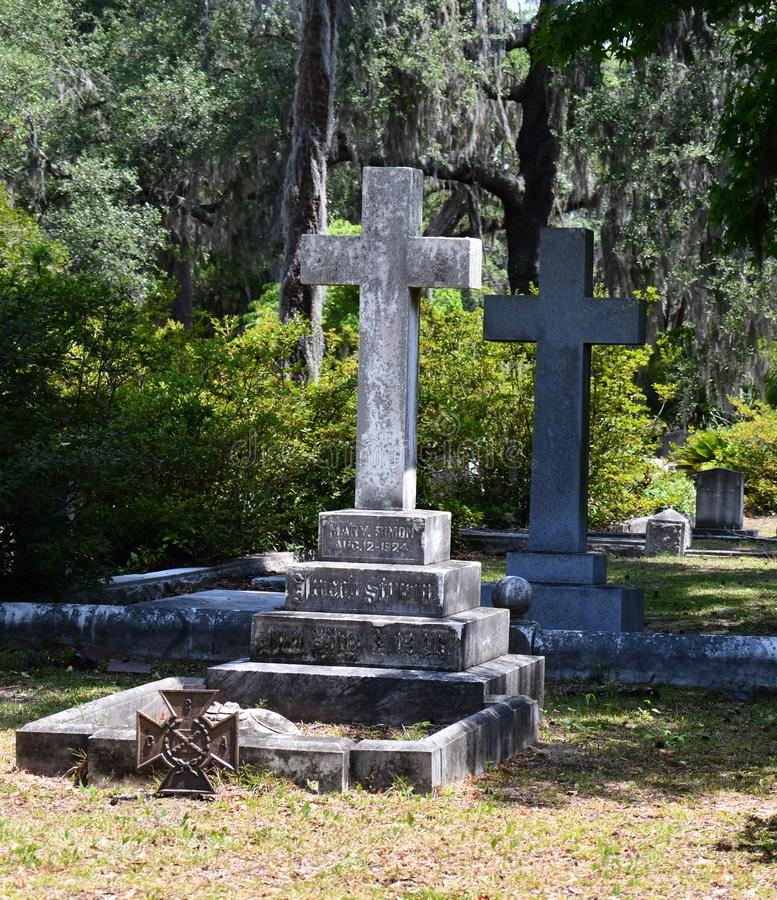 Cemetery Headstone at Savannah Georgia historic cemetery. Granite cross headstone featured at the oldest cemetery in Savannah Georgia, surrounded by trees stock images