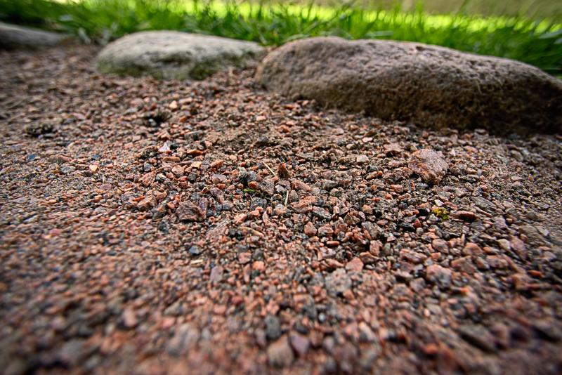 Granite pebbles background large stones and grass stock photos