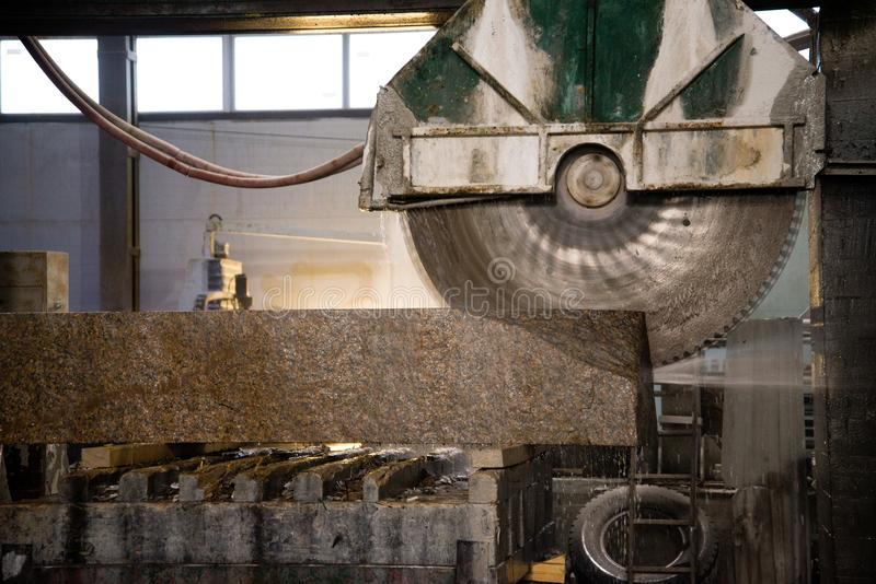 Granite processing in manufacturing. Cutting granite slab with a circular saw. Use of water for cooling. Industrial sawing of. Granite processing in royalty free stock photo