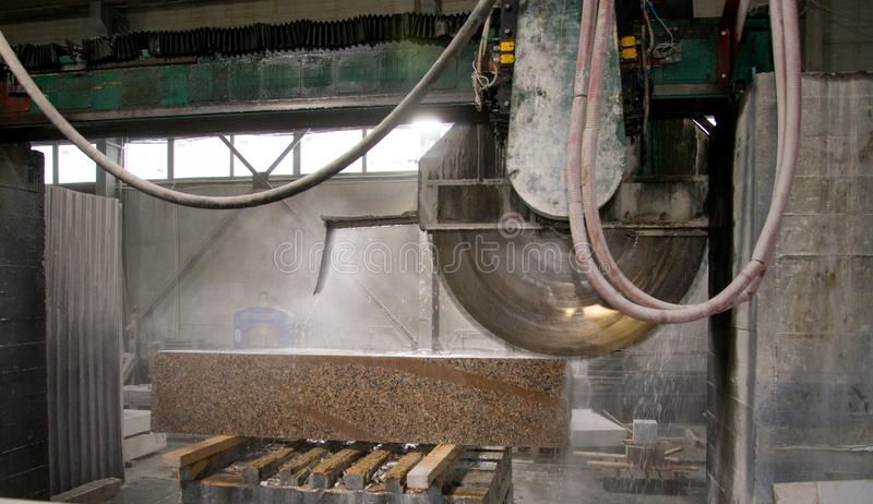 Granite processing in manufacturing. Cutting granite slab with a circular saw. Use of water for cooling. Industrial sawing of. Granite processing in royalty free stock photos