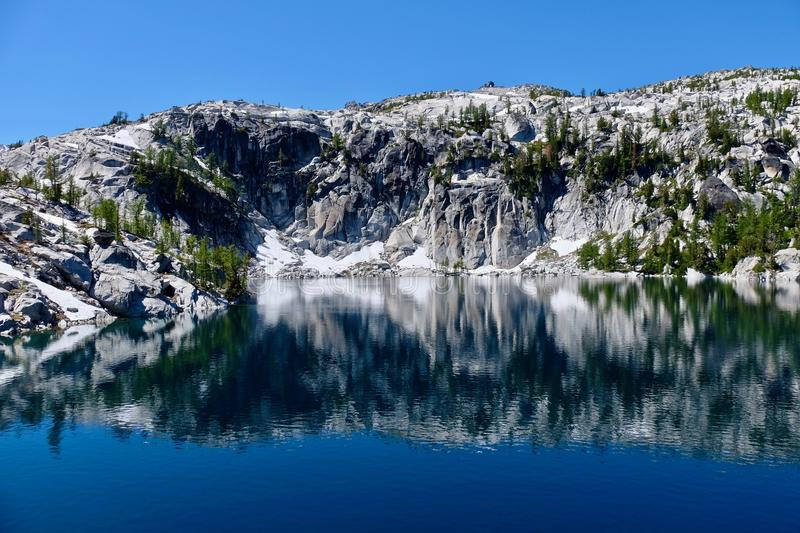 Granite rocks and reflections in calm water. Lake Vivian in The Enchantments lakes basin. Leavenworth. Seattle. WA. United States royalty free stock image