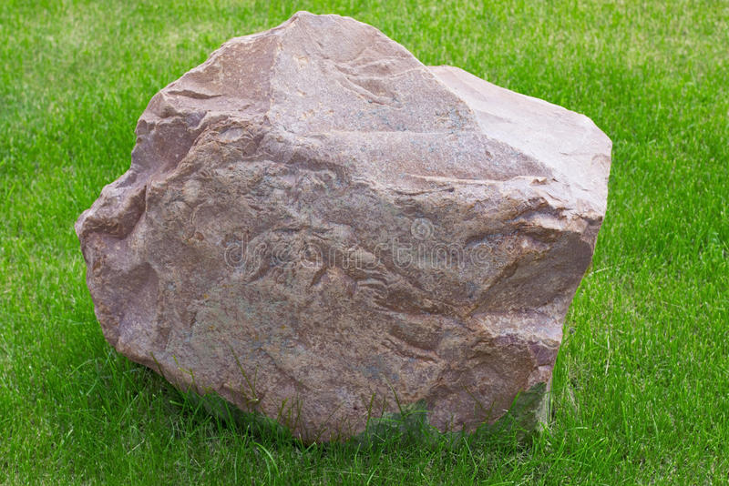 The granite stone on the grass royalty free stock photos