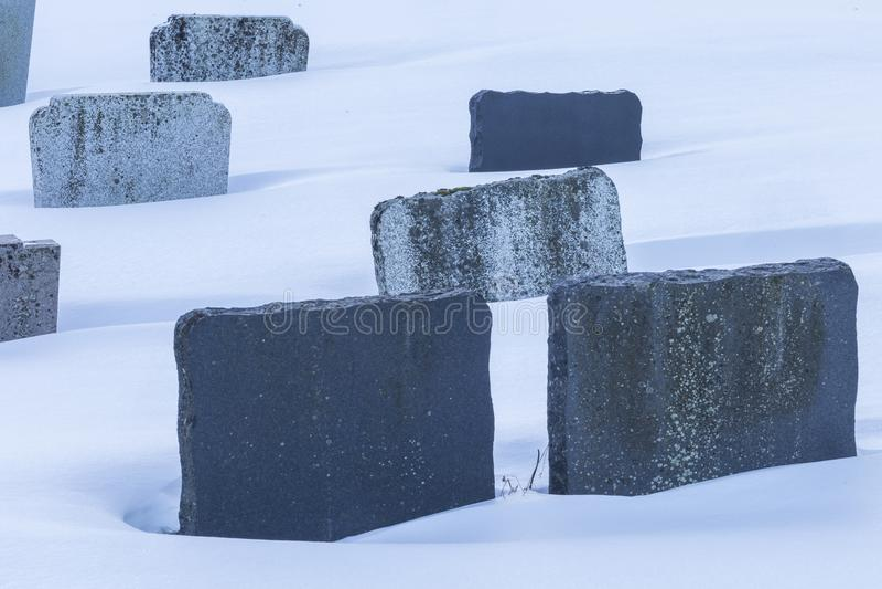 Granite textured tombstones emerging from winter snow in graveyard stock images