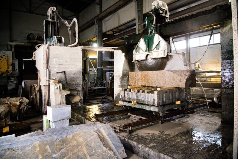 Granito que processa na fabricação Laje do granito do corte com uma serra circular Uso da água para refrigerar Ver industrial de foto de stock