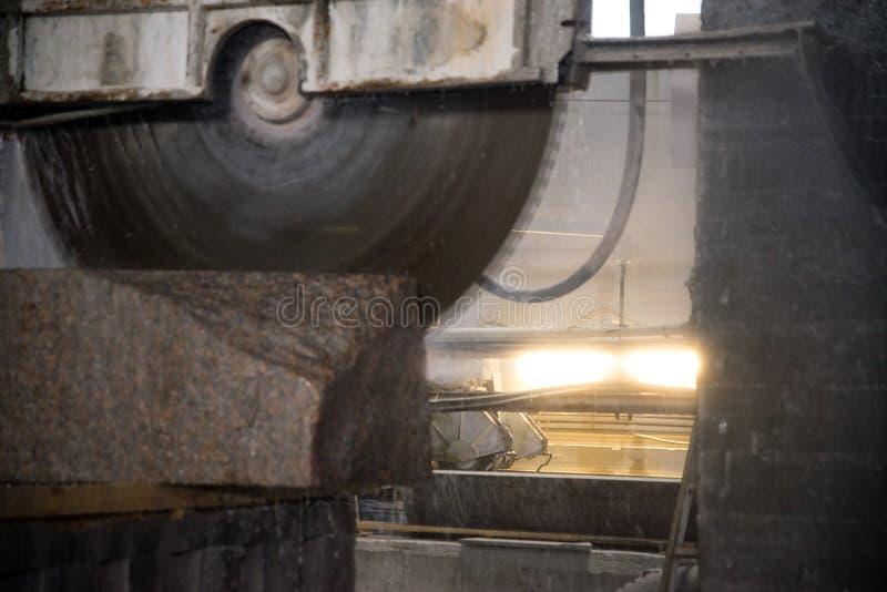 Granito que processa na fabricação Laje do granito do corte com uma serra circular Uso da água para refrigerar Ver industrial de fotos de stock