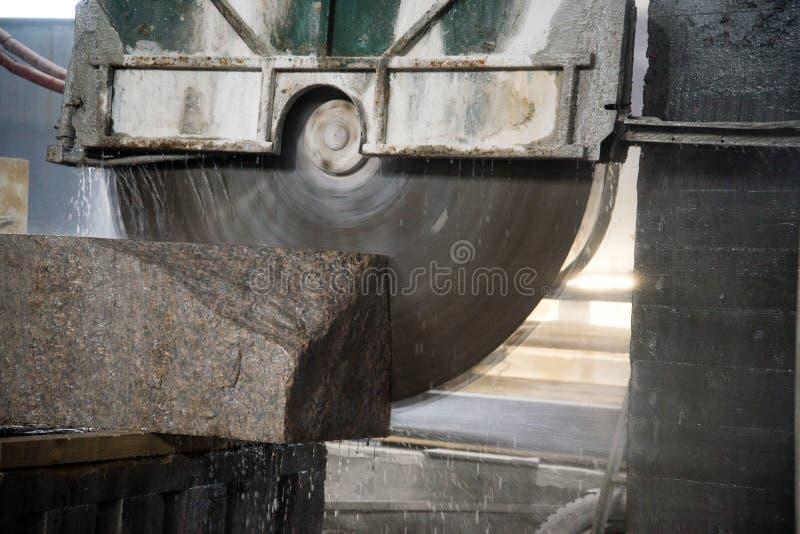 Granito que processa na fabricação Laje do granito do corte com uma serra circular Uso da água para refrigerar Ver industrial de imagens de stock royalty free