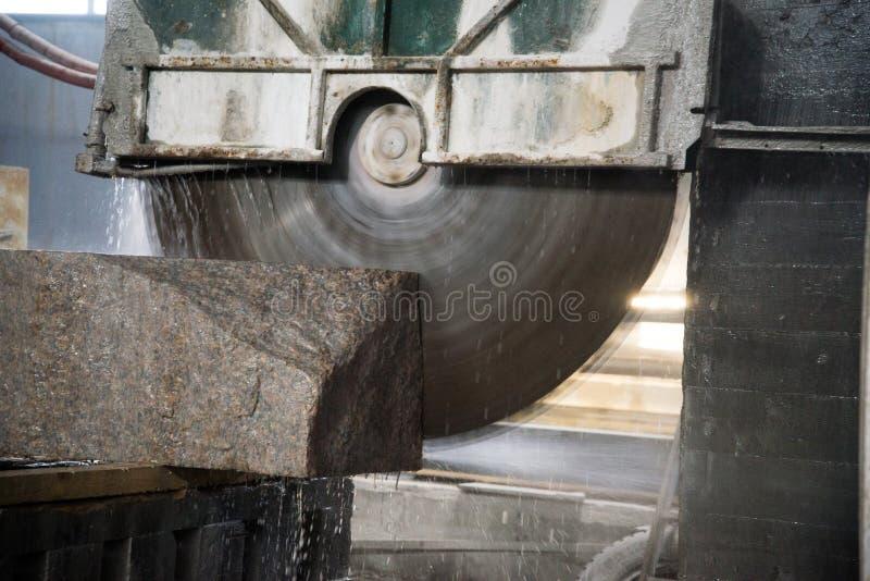 Granito que processa na fabricação Laje do granito do corte com uma serra circular Uso da água para refrigerar Ver industrial de imagens de stock