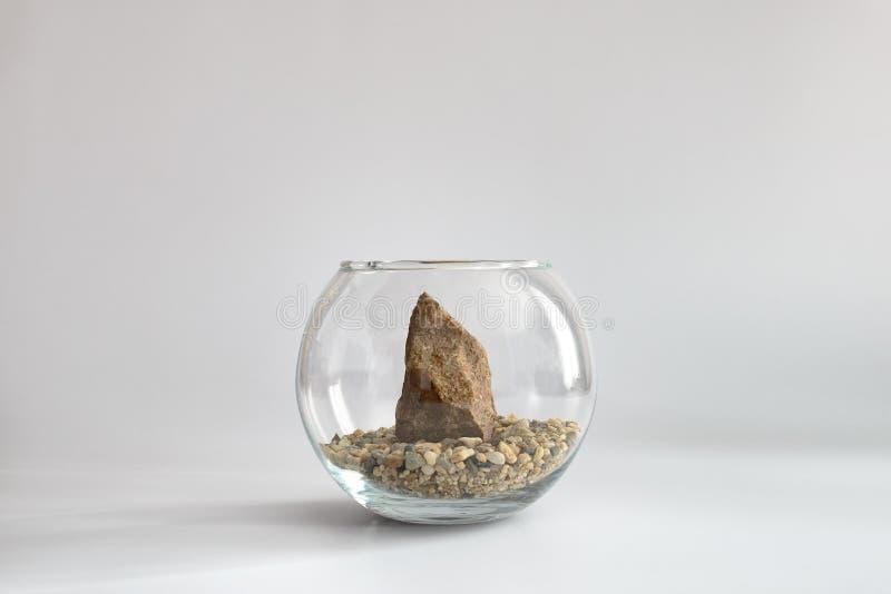 Granitsten på sand i exponeringsglasakvarium Minsta begrepp arkivbild