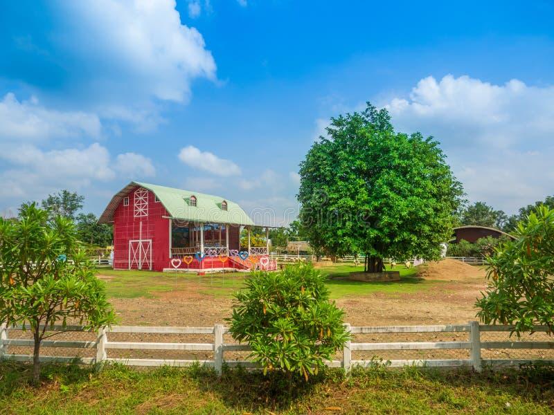 Granja de granero rojo con un gran árbol en el campo imagenes de archivo