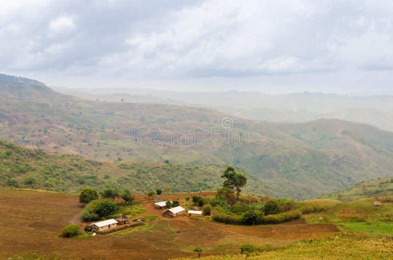 Granja tradicional en la región de la carretera de circunvalación del Camerún, África con las montañas en la distancia imagen de archivo
