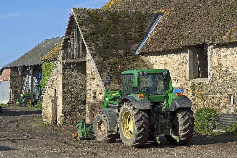 Granja vieja de la opinión del pueblo y nuevo tractor imagen de archivo