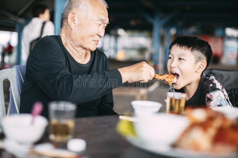 Granjero asiático de alto rango alimentando a su nieto en un restaurante fotografía de archivo