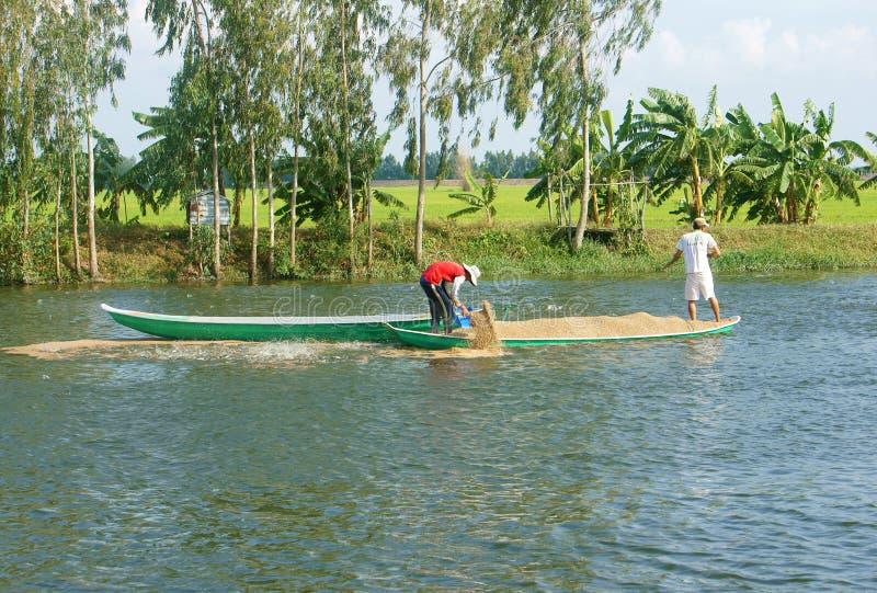 Granjero asiático que alimenta, estanque de peces, industria pesquera fotos de archivo