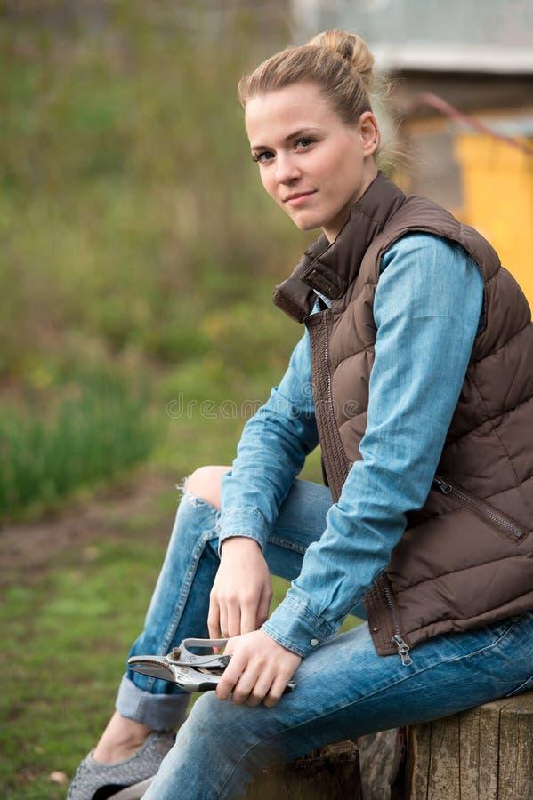 Granjero bonito de la muchacha que descansa con la herramienta de ramas del corte en jardín del ` s del granjero de la primavera fotos de archivo libres de regalías