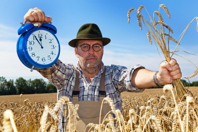 Granjero con 11:55 del reloj fotos de archivo
