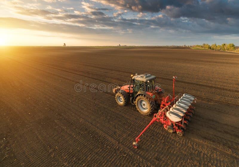Granjero con el sembrador del tractor - la siembra cosecha en el campo agrícola