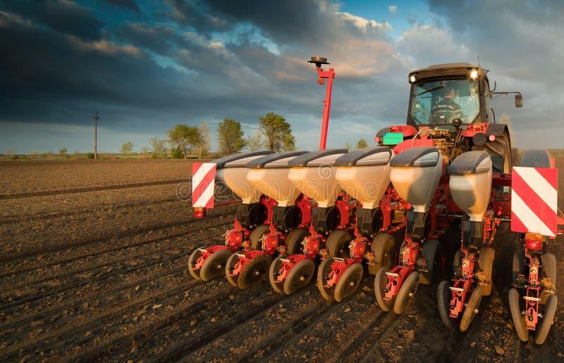 Granjero con el sembrador del tractor - la siembra cosecha en el campo agrícola imagenes de archivo