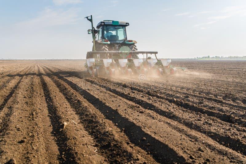 Granjero con el sembrador del tractor - la soja de la siembra cosecha en f agrícola imagenes de archivo