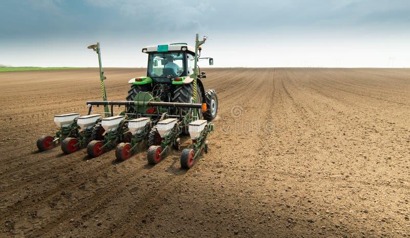 Granjero con el tractor que siembra sembrando cosechas en el campo agr?cola foto de archivo