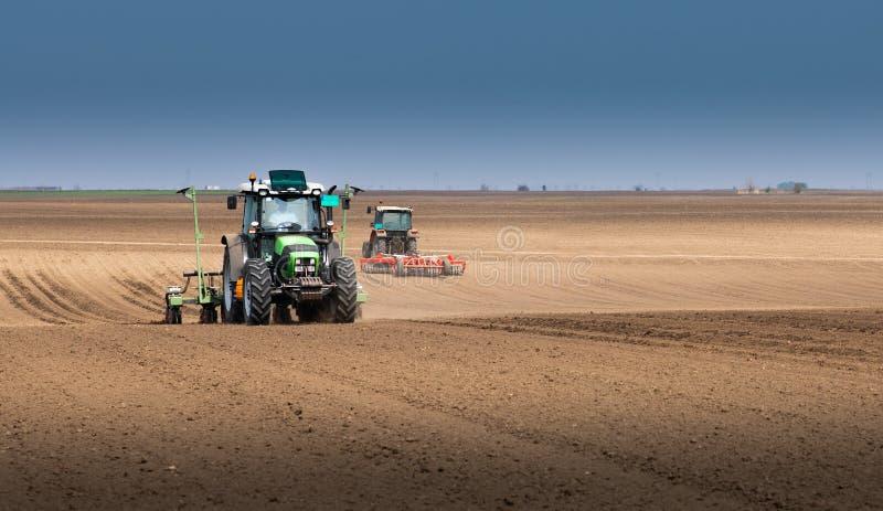 Granjero con el tractor que siembra sembrando cosechas en el campo agr?cola imagenes de archivo