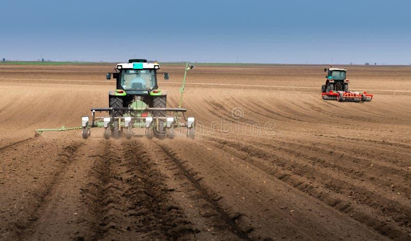 Granjero con el tractor que siembra sembrando cosechas en el campo agr?cola fotografía de archivo libre de regalías