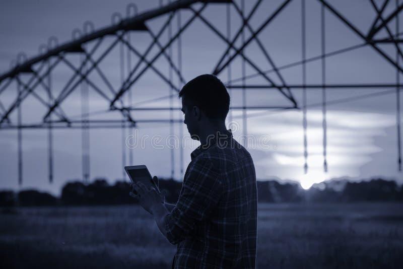Granjero con la tableta delante del sistema de irrigación fotos de archivo