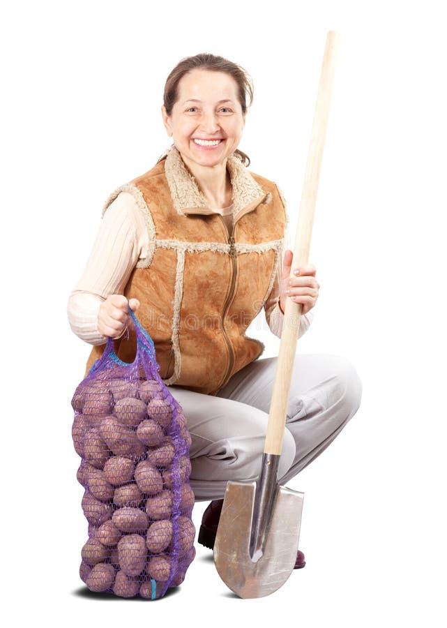 Granjero con las patatas y la espada cosechadas imagenes de archivo