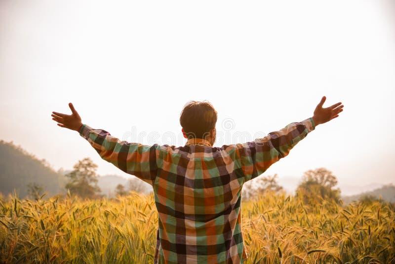 Granjero del hombre joven en los brazos permanentes de la camisa de scott aumentados en un campo imagen de archivo libre de regalías