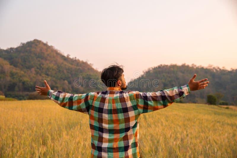 Granjero del hombre joven en los brazos permanentes de la camisa de scott aumentados en un campo imágenes de archivo libres de regalías