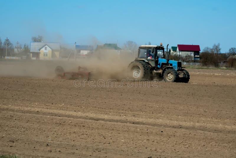 Granjero en el tractor que prepara la tierra con el cultivador del semillero como parte de actividades pre sembradas en la estaci fotos de archivo