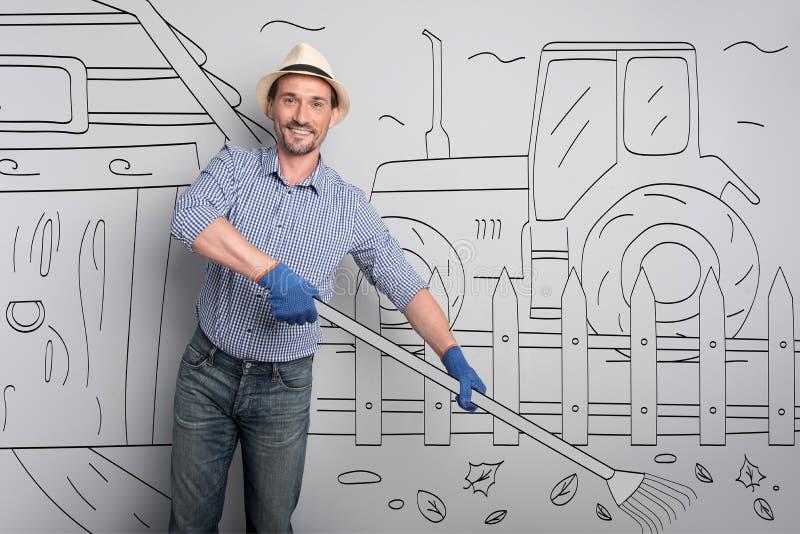 Granjero feliz que limpia en la yarda imagen de archivo