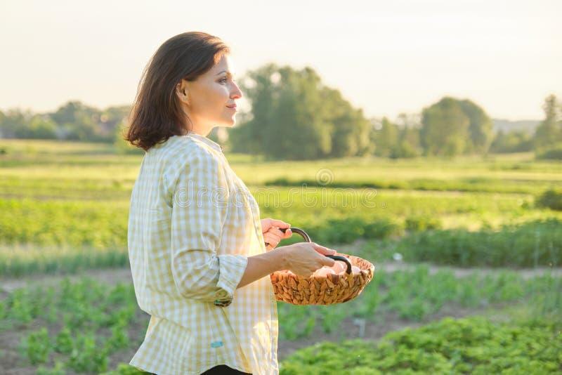 Granjero hermoso maduro de la mujer con la cesta de huevos frescos fotografía de archivo libre de regalías