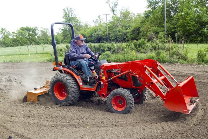 Granjero mayor Tilling His Garden con un tractor compacto 4x4 imagen de archivo